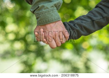 Road to life. Hands. Father's and his son's hands. Dad leading son over autumn nature outdoor. Male and children hands close up. Family, trust, protecting, care, parenting, parenthood concept.