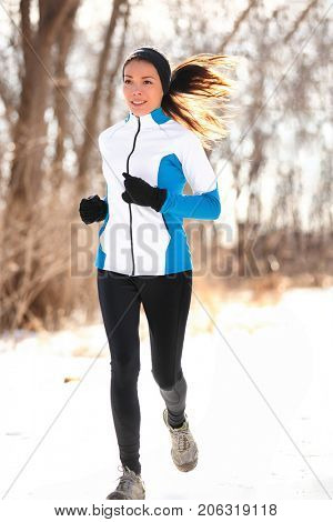 Winter run jogging fit runner girl running outdoor in snow. Asian woman athlete training outside wearing cold weather clothing jacket, tights, gloves and headband.