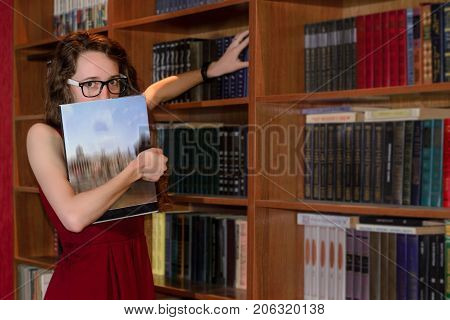Beautiful Young woman  hiding face behind book looking at camera in library
