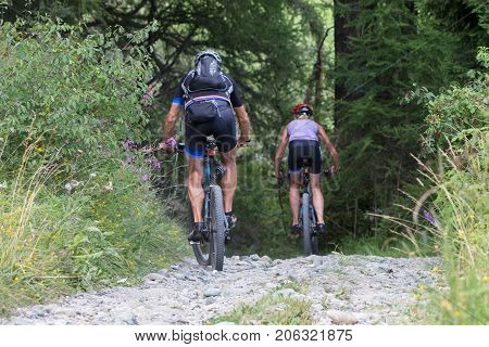 Urecognisable Mountainbikers On A Gravel Road