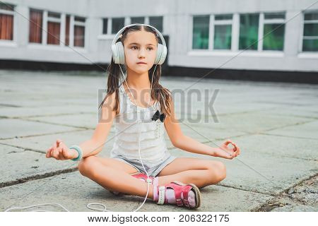 beautiful girl sitting and listening music with headphones, nice girl in a light sweater with a black bow listening music on headphones. yoga pose