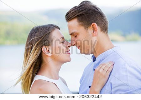 Picture of beautiful young couple cuddling and posing outdoor