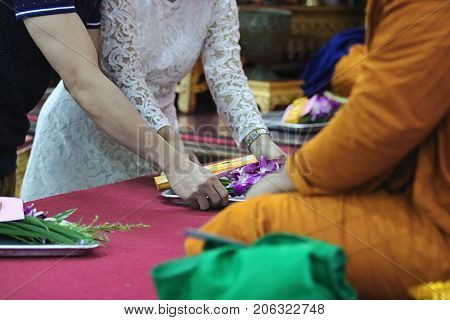 Selective focus on hands of young couple make merit to monks in buddhism temple