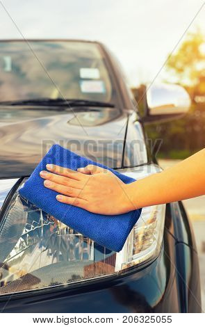 Asian woman's hand wiping headlight of car by micro fiber cloth.