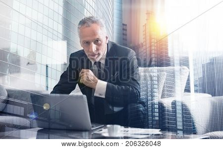Professional attitude. Senior sucessful businessman sitting on the couch and using his laptop while expressing confidence