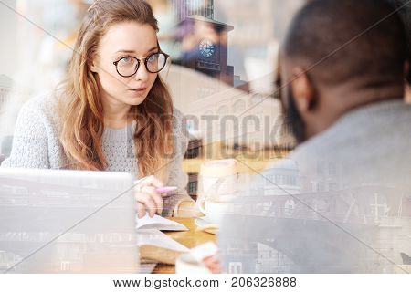 Total attention. Lovely young girl with glasses listening to her friends carefully while sitting at the table and working with notes