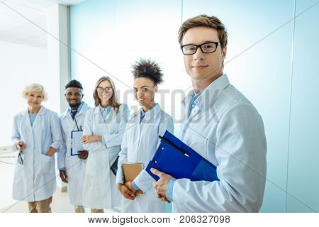 Multiracial group of smiling medical interns in lab coats standing in a row with clipboards and stethoscopes