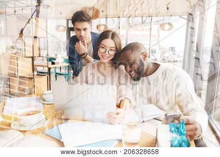 Complete attention. Concentrated diligent colleagues looking at the screen of the laptop and expressing huge interest while sitting at the table