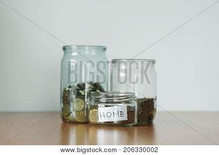 Coins In Glass Jars For Different Needs, Money Boxes. Distribution Of Cash Savings Concept. Home Sti