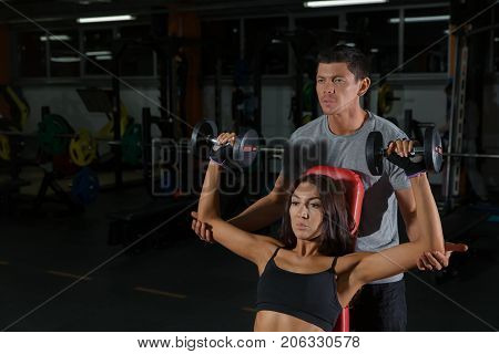 Athletic couple training with dumbbells in sport gym. Active lifestyle man and woman in fitness club