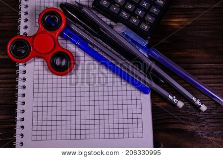 Spinner And Different Stationeries On Wooden Desk. Top View