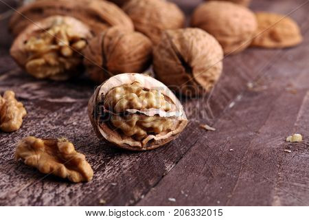 Walnut kernels and whole walnuts on rustic old wooden table.