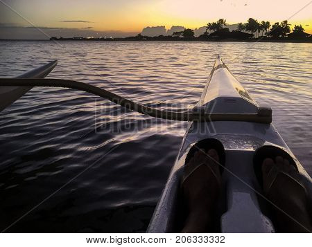 First person view of solo outrigger canoe paddler with outrigger at sunset