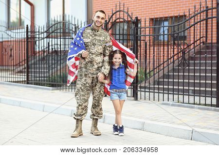 US army soldier with little daughter and USA flag