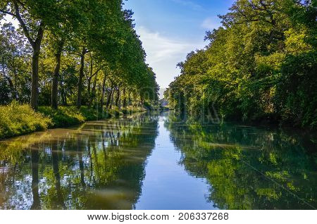Beautiful Canal du Midi, sycamore trees reflection in water, Southern France