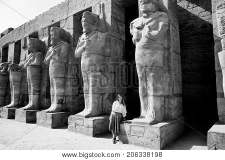 Girl admiring statues near famous ancient temple in Luxor, Egypt