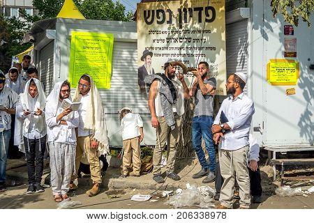 Uman Ukraine - 21 September 2017: Rosh Hashanah Jewish New Year. Mass prayer of pilgrims of Hasidim on the street where Rebbe Nachman the founder of Hasidism is buried. Jewish hasid blows Shofar.