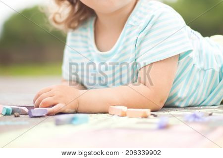 Sunny and warm summer days and happy chilhood. Cute little girl drawing with chalk crayons outdoors