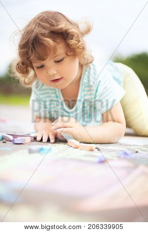 Cute Toddler Girl Drawing With Piece Of Color Chalk