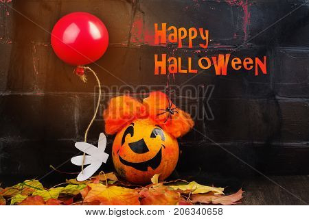 Scary red hair clown made from pumpkin, holding red balloon. Spooky dark Halloween background. Greeting card, space for text