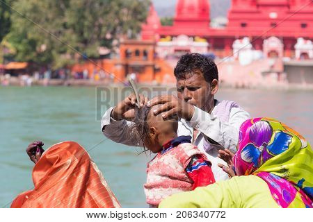 Haridwar, India - March 20, 2017: Man Shaving Off Hairs For Young Hindu Devotee Initiation On The Ga