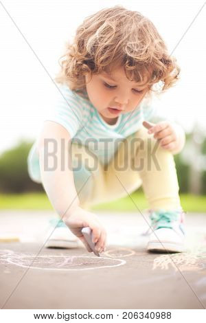 Sunny summer days and happy chilhood. Cute little girl drawing with chalk crayons outdoors