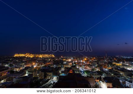 Jaisalmer Cityscape At Dusk. The Majestic Fort Dominating The City. Scenic Travel Destination And Fa