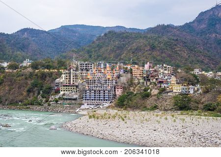 Cityscape Of Rishikesh At Sunset, Holy Town And Travel Destination In India. Colorful Sky And Clouds