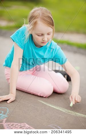 Sunny and warm summer days and happy chilhood lisure time. Cute little girl drawing with chalk crayons at the asphalt alone. Summer vacation.