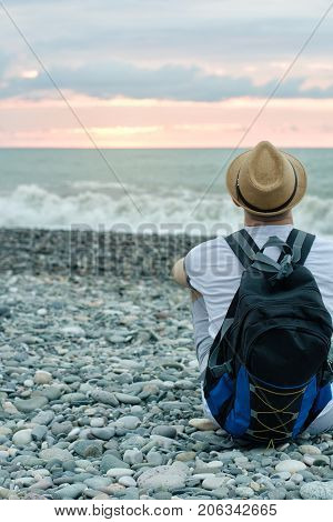 Guy In Hat And With Backpack Sitting On The Beach Against The Backdrop Of The Sea And Sunset Sky. Ba