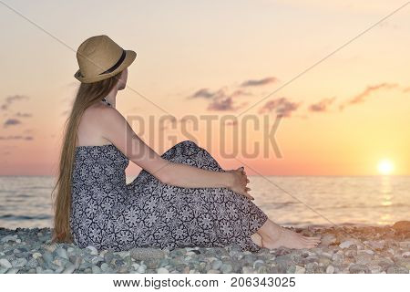 Girl In A Hat Sitting On A Background Of The Sea At Sunset
