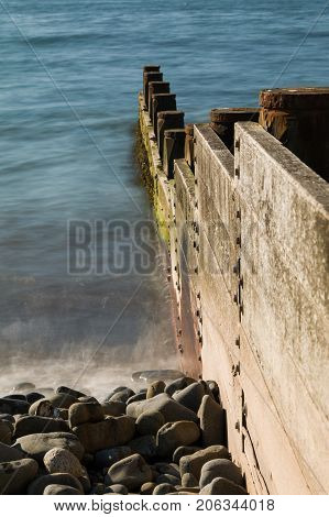 North Wales Coast Wooden sea defences. Blue sea stones on beach at the side of the wooden defences.