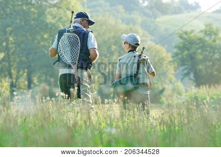 Daddy and son walking in field, fishing day