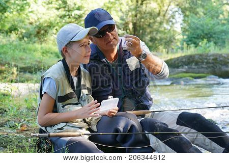 Dad helping son to choose flies for fishing line