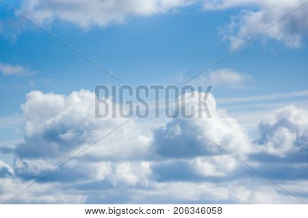 White cumulus clouds are on a blue sky