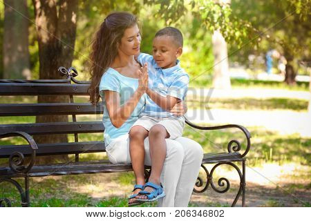 Young woman playing with adopted African American boy while sitting on bench in park