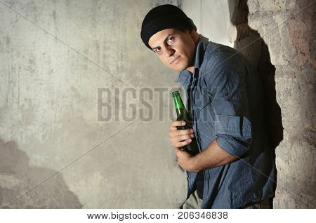 Man with bottle of alcohol in abandoned building