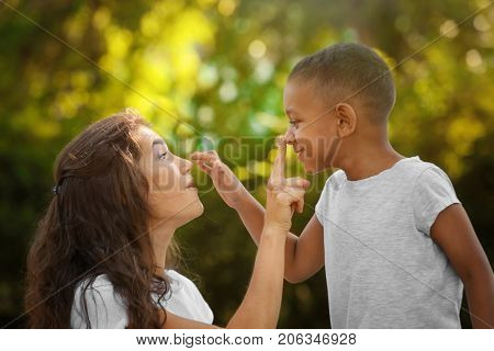 Young woman with adopted African American boy outdoors