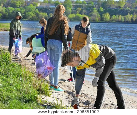 Young people cleaning beach area. Volunteering concept