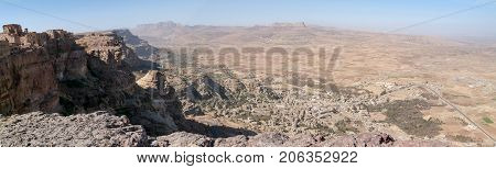 Red rocks and decorated old houses overview of Shibam valley seen from Kawkaban on Yemen