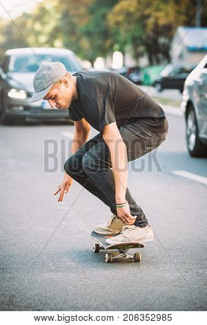 Pro Skateboard Rider In Front Of Car On City Road