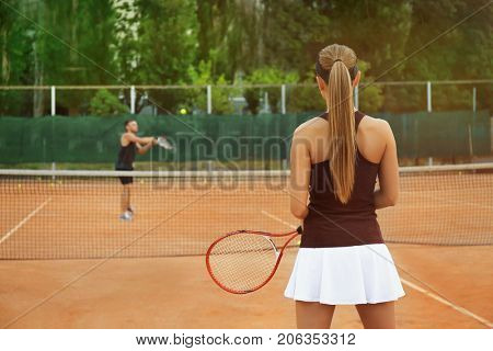 Young woman and man playing tennis on court