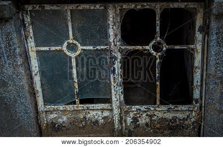 Broken window on a crypt in a cemetery