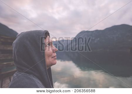Nostalgic portrait of lonely melancholic adult female with hopeful look towards the sky standing on the lake shore in misty overcast morning retro toned image