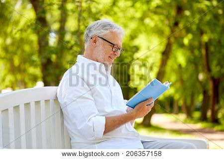 old age, retirement and people concept - happy senior man reading book sitting on bench at summer park