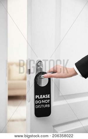 Person opening door of hotel room with sign PLEASE DO NOT DISTURB on handle