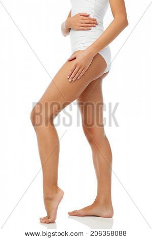 beauty, people, anticellulite and bodycare concept - legs of beautiful young woman in white underwear