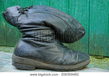 Old black leather boot near the green wall
