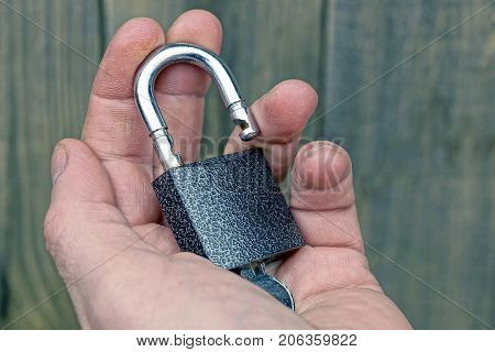 An open gray padlock with a key on the open palm