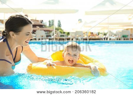 Mother and baby with inflatable ring in swimming pool